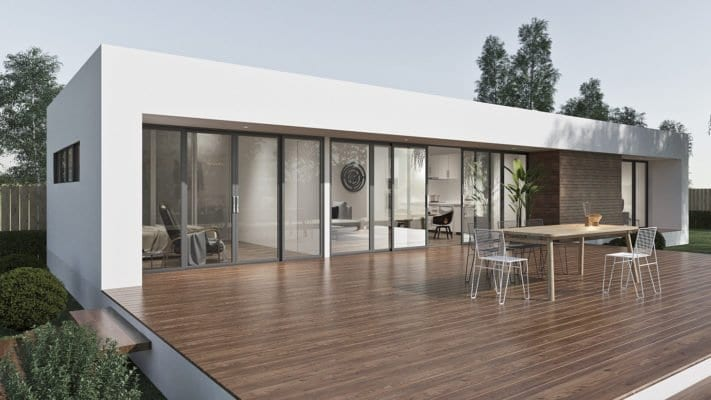 Spacious white flat with wooden floor and stairs, glass windows and doors. Sorrounded by trees, plants, and grass. With TV, sofa and bed inside the flat. Have a wooden table outside with five steel chairs.